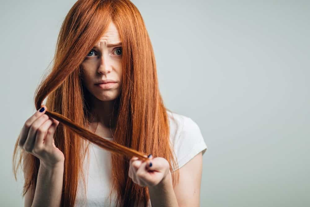 Woman looking troubled with her long red dry hair.