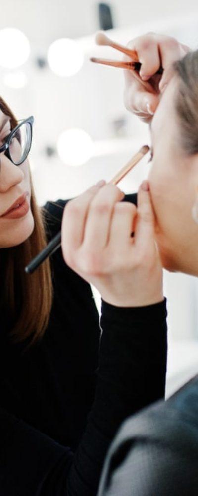 A makeup artist applies eyeshadow on a woman.