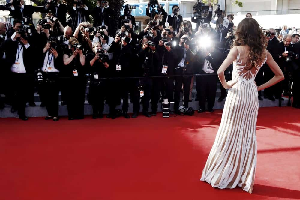 Back view of an actress posing at a red carpet in front of the press.