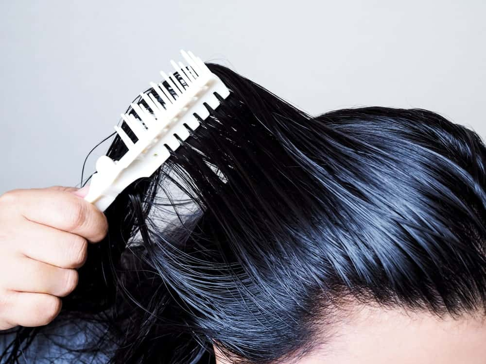 Combing black oily hair.