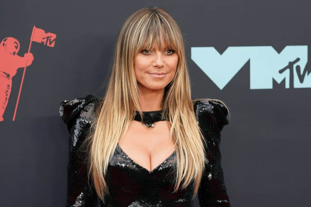 Looking fierce, Heidi Klum flaunted her straight blonde hair with subtle layers and bangs along with a black sequin dress which she wore at the MTV Video Music Awards held on August 26, 2019.