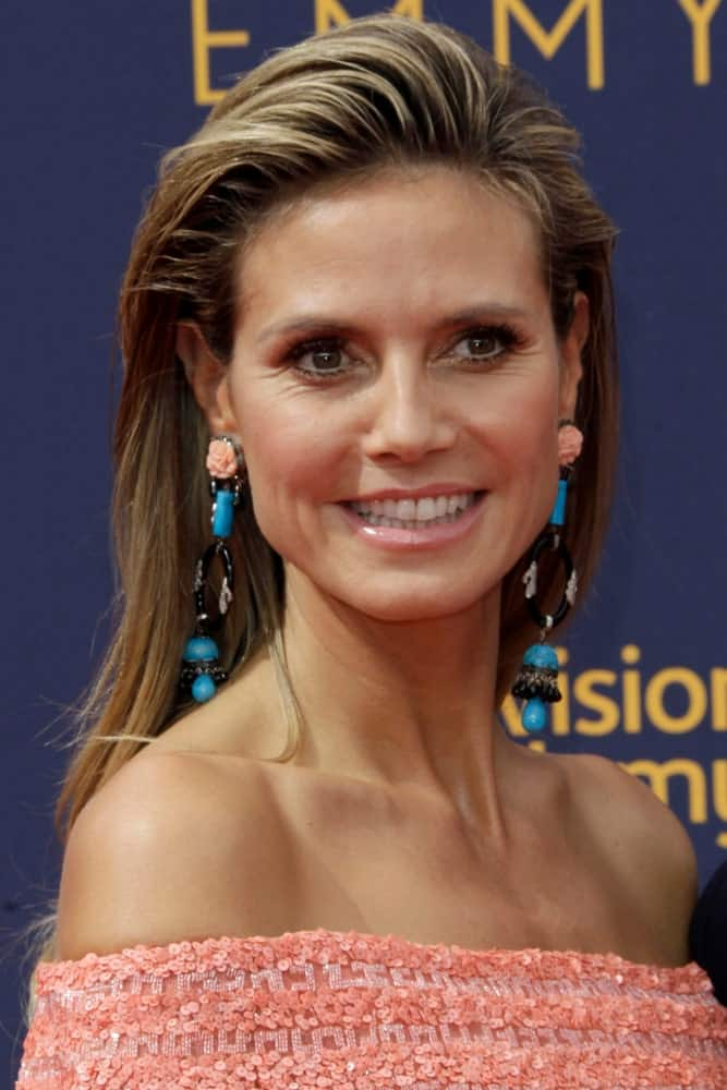 Heidi Klum exhibits a cool and dainty look showing off a cool side swept hairstyle that's truly captivating. Chandelier earrings and a coral pink off-shoulder dress complete the look.