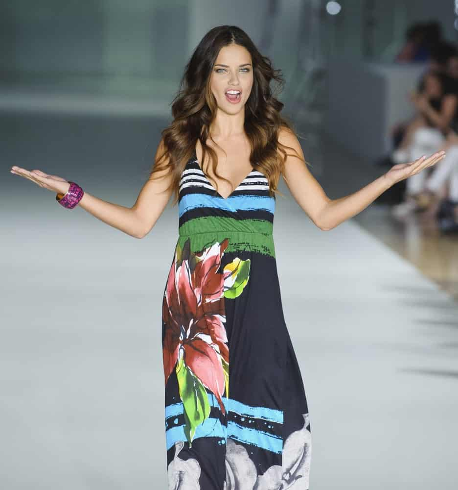 Brazilian model Adriana Lima walks on the Desigual catwalk during the 080 Barcelona Fashion runway on July 09, 2013 in Barcelona, Spain. She was relaxed and confident in her colorful beach dress and beach curls tousled and loose.