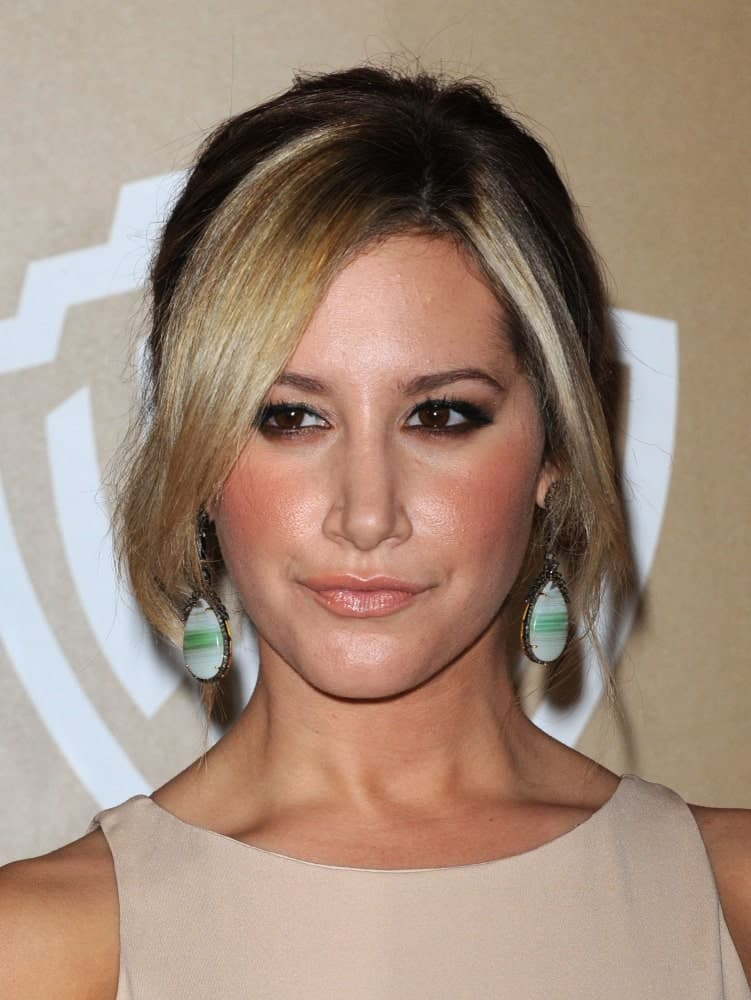 On January 13, 2013, Ashley Tisdale attended the WB/In Style Golden Globe Party with a messy updo incorporated with curtain bangs. Statement earrings and a classic nude dress completed the look.