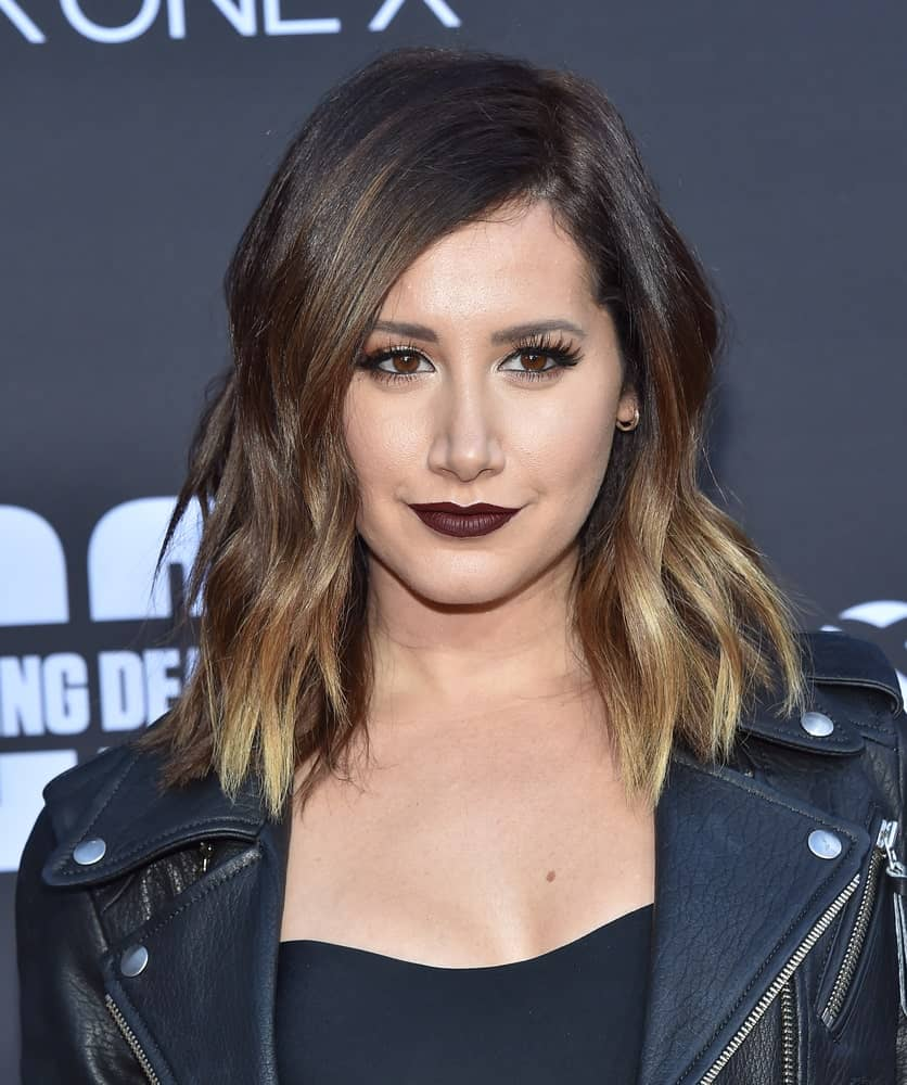 The actress rocks a highlighted beach wave perm on her outgrown hair during the 'The Walking Dead' Season 8 Premiere on October 22, 2017. It complements well with her dark lipstick and black getup.