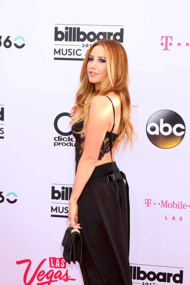 Ashley Tisdale attended the 2017 Billboard Music Awards - Arrivals at the T-Mobile Arena on May 21, 2017, with a sexy black outfit accentuated by her long wavy hair with subtle layers.
