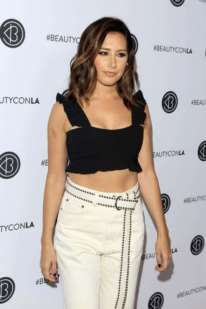 The actress arrives at the 5th Annual Beautycon Festival Los Angeles held on August 12, 2017, with white high waisted pants and a cute black top. She finishes the look with a simple loose hairstyle.
