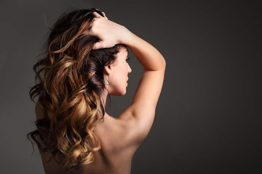 Back profile of a woman with hot perm.