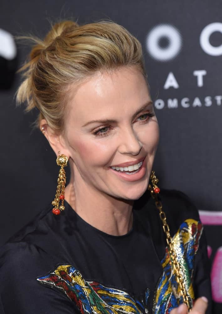 "Charlize Theron was seen at the ""Tully"" Los Angeles Premiere on April 18, 2018, in a black printed dress and her blonde hair arranged into a voluminous updo hairstyle."
