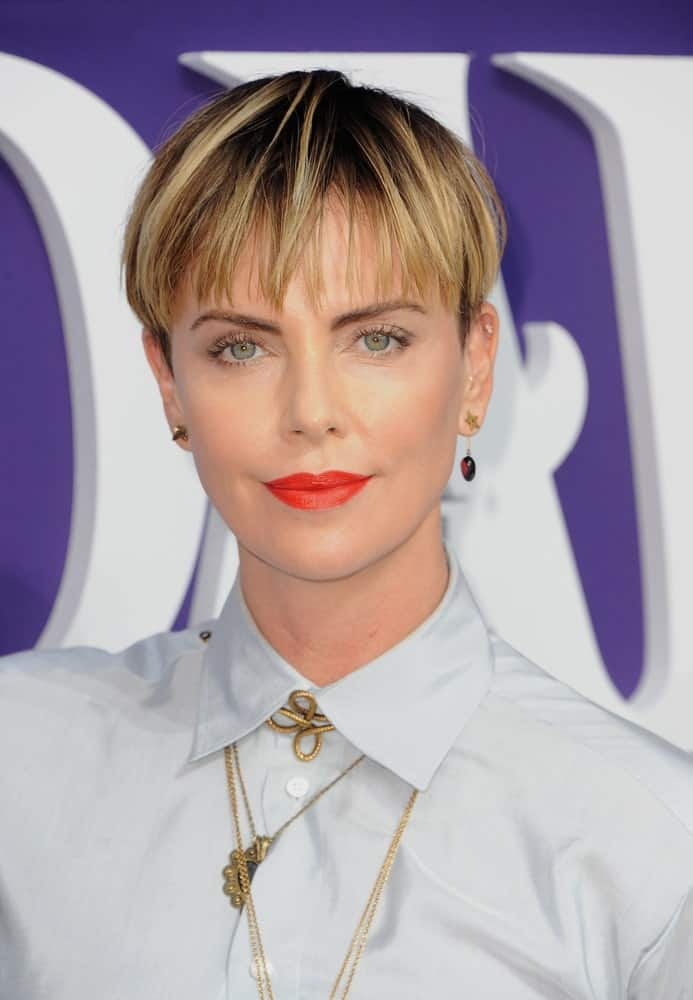 Charlize Theron wore a button-down polo and eye-catching red lipstick at the Los Angeles premiere of 'The Addams Family' held on October 6, 2019. She paired it with thin, airy bangs that are highlighted to give it some dimensions.