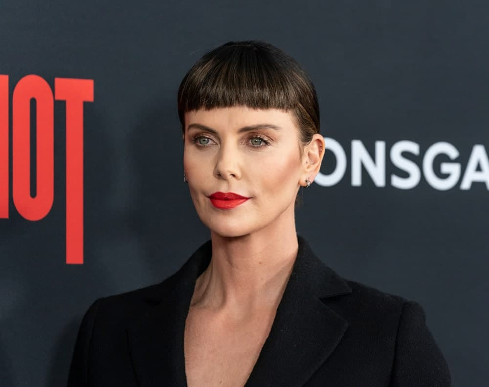 During the premiere of Long Shot at AMC Lincoln Center Theater on April 30, 2019, Charlize Theron flaunted a neat updo with short blunt bangs. She finished the look with a black suit and red lipstick.