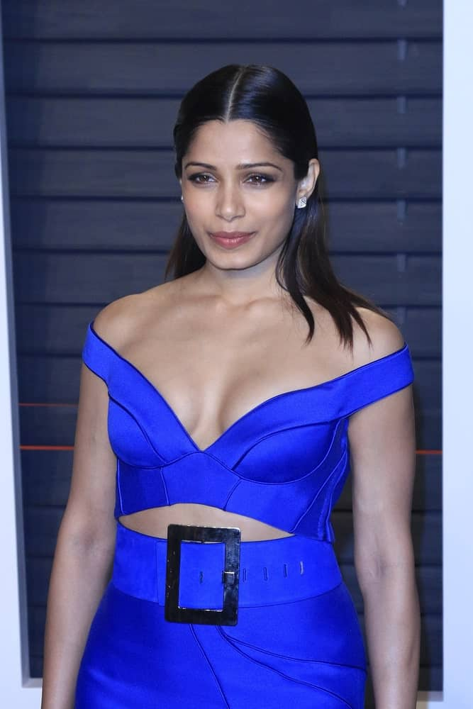 The beautiful actress Freida Pinto attended the 2016 Vanity Fair Oscar Party last February 28, 2016 in Beverly Hills, California wearing a bright blue dress with a slick half-up straight black hair on her shoulder.