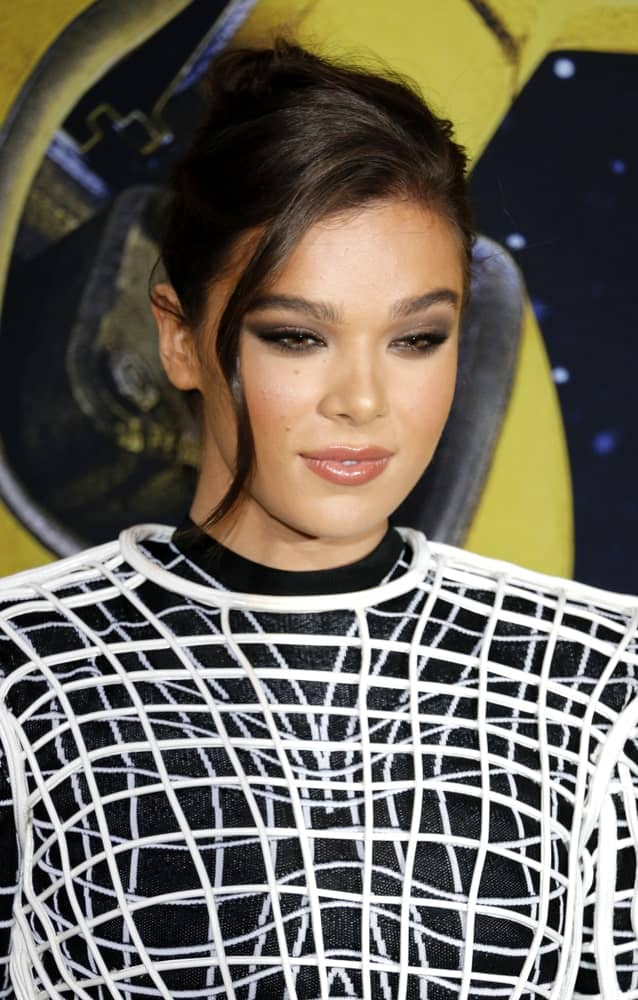 Hailee Steinfeld shows off a neat upstyle hairstyle complemented by a wavy tendril that falls down her cheek at the World premiere of 'Bumblebee' held on December 9, 2018.  It was completed with a trendy black dress that perfectly suited the theme.