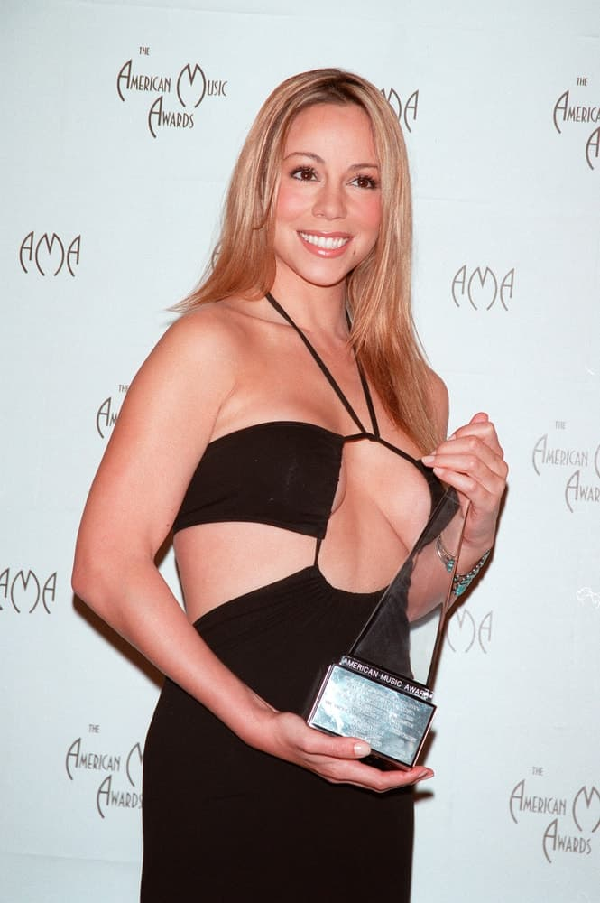 Mariah Carey holds a trophy at the American Music Awards in Los Angeles on January 17, 2000, where she received a special career award.