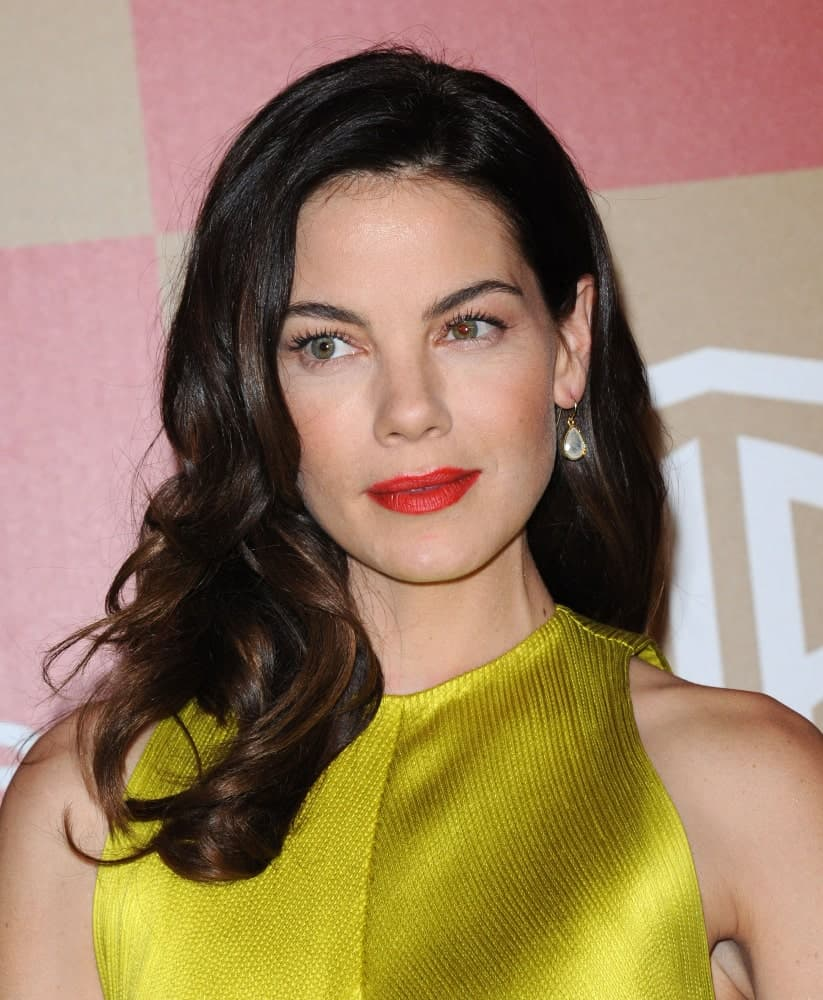 Michelle Monaghan arrives at the In Style Golden Globe Party on January 13, 2013 in Hollywood wearing a golden outfit that perfectly complements her side-swept dark curls with subtle highlights for a bit of depth.