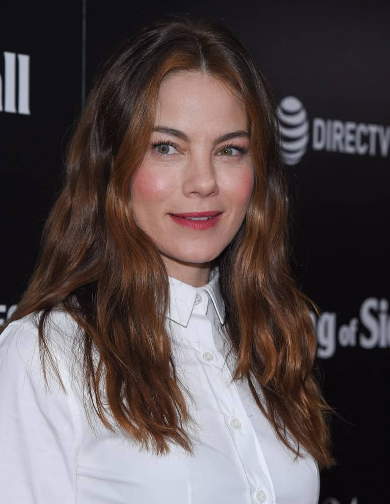 "Michelle Monaghan arrives for the ""The Vanishing of Sidney Hall"" LA Screening on February 22, 2018 in Hollywood, CA with a tousled and loose hairstyle that has auburn highlights. These stand out against her stark white blouse and dazzling smile."
