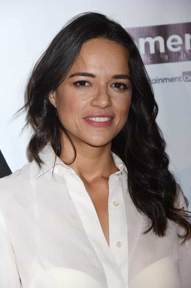 Back in February 2015, Michelle Rodriguez had long straight raven hair that was styled into this wavy and tousled masterpiece contrasting her white sheer blouse.