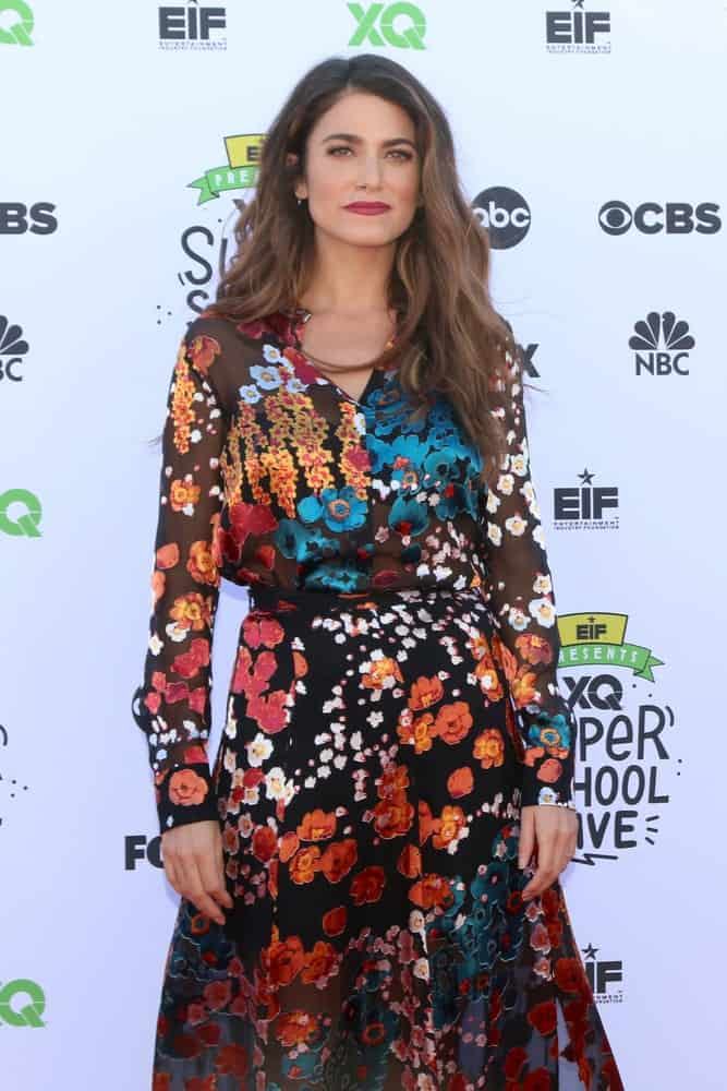 Nikki Reed wearing a long floral dress paired with a voluminous wavy hairstyle that's dyed in toffee brown at the EIF Presents: XQ Super School Live at the Barker Hanger on September 8, 2017.