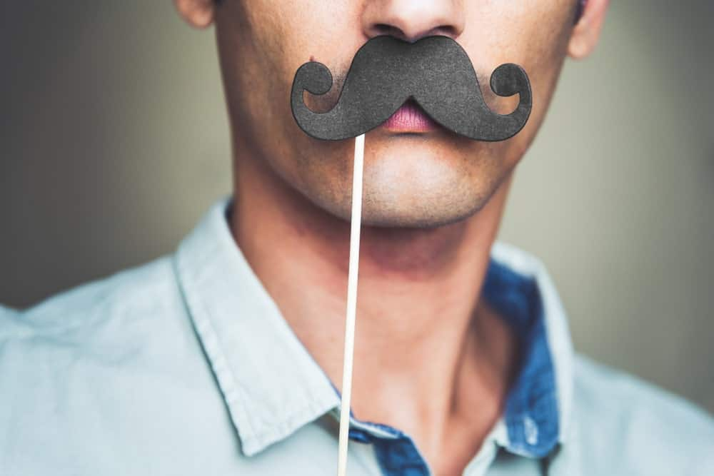 Man wearing a fake paper mustache.