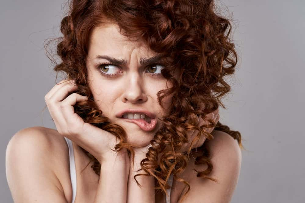 Curly-haired woman looking scared.