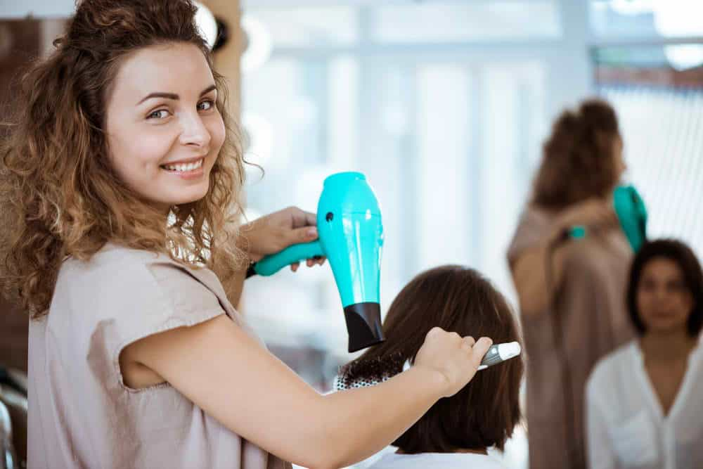 A hairdressser looks into the camera with a smile while hairblowing a customer's hair.