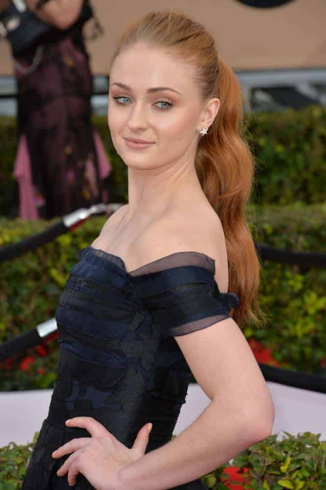 Sophie Turner looked stunning in her simple dress and her gorgeous reddish brown long hair was styled into a high ponytail with cascading waves at the back.