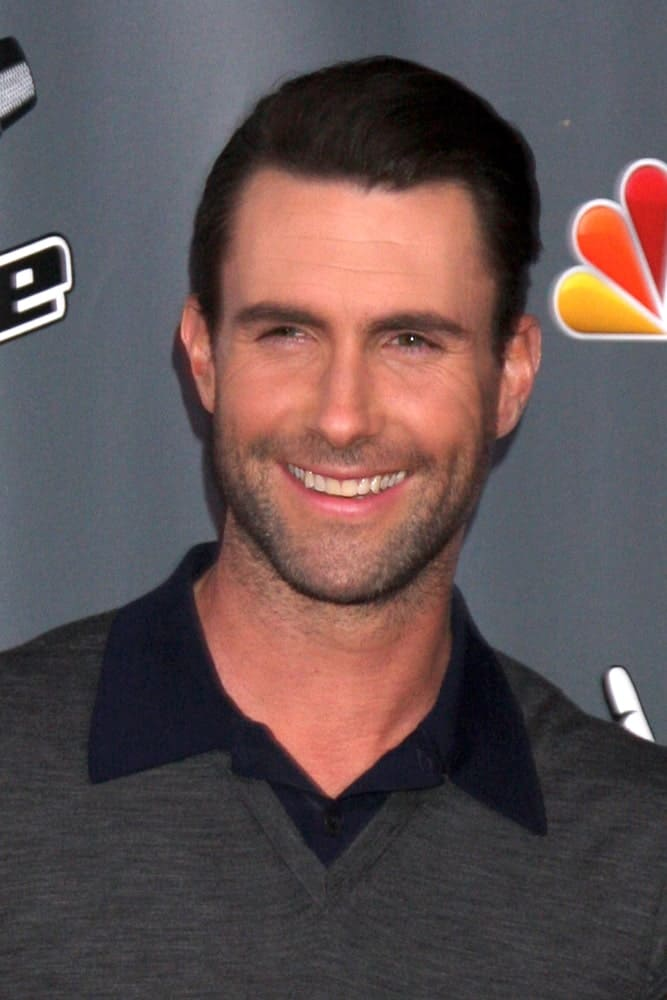 Adam Levine's brilliant smile flashed with his trimmed beard and brushed back hairstyle with a neat fade finish at the The Voice Season 5 Judges Photocall at Universal Studios Lot on November 7, 2013 in Los Angeles, CA.