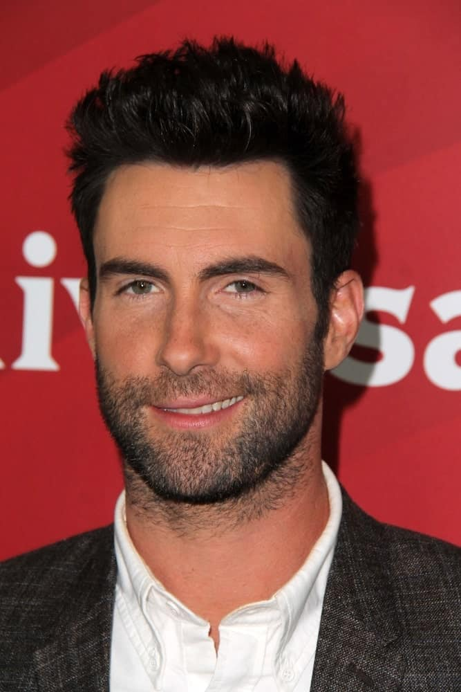 Adam Levine's sexy confident smile worked quite well with his trimmed beard and spiked fade hairstyle at the NBC Universal's