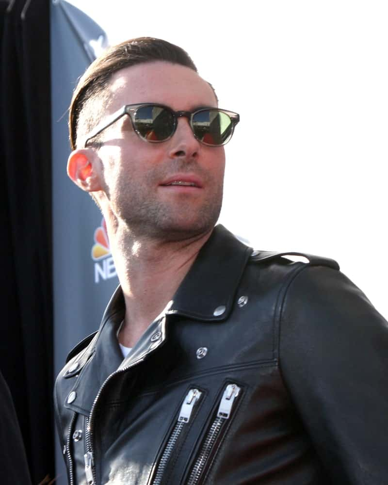 Adam Levine was edgy with his black leather jacket and brushed back undercut hairstyle at the