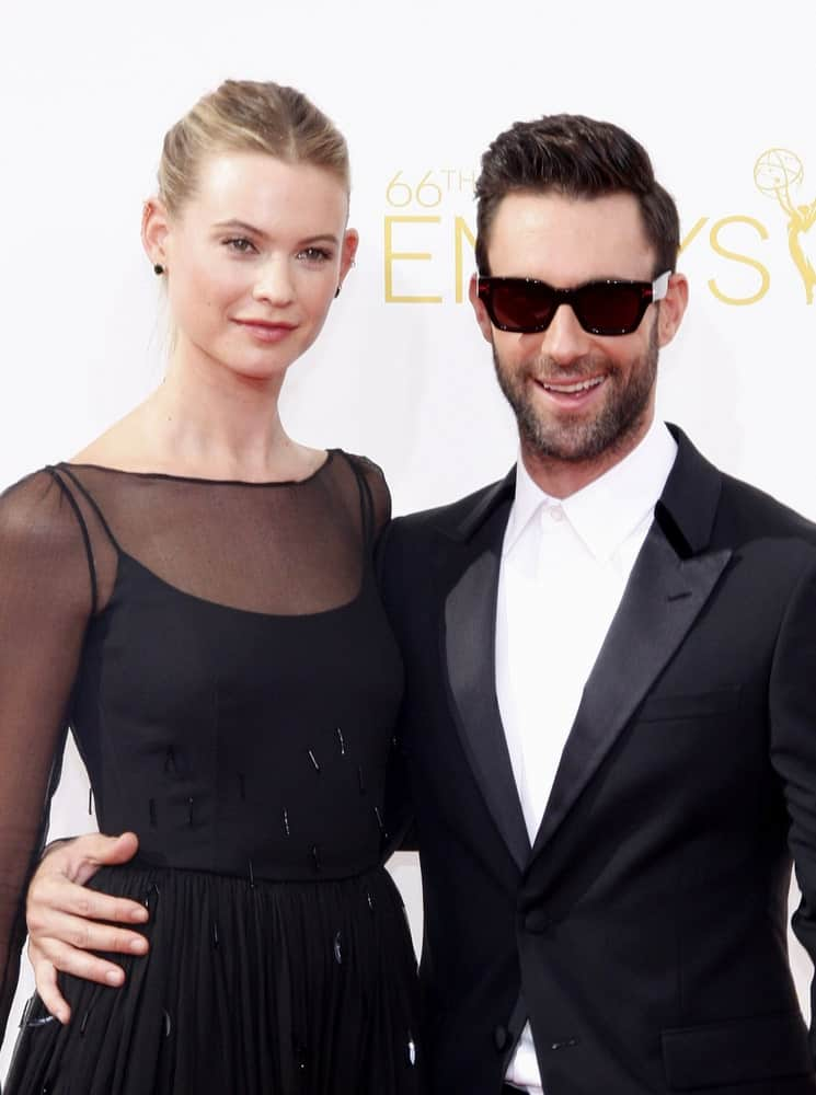 Behati Prinsloo and Adam Levine were in matching black outfits at the 66th Annual Primetime Emmy Awards in Los Angeles on August 25, 2014. Levine paired this with a slick pompadour hairstyle with slight side part.