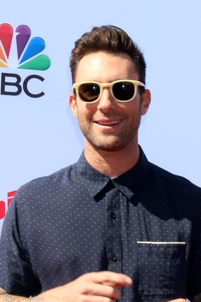 Adam Levine looked hip and handsome with his sunglasses and side-swept pompadour hairstyle that complemented his button-down shirt at the The Voice Red Carpet Event at the Hyde on April 21, 2016 in Los Angeles, CA.