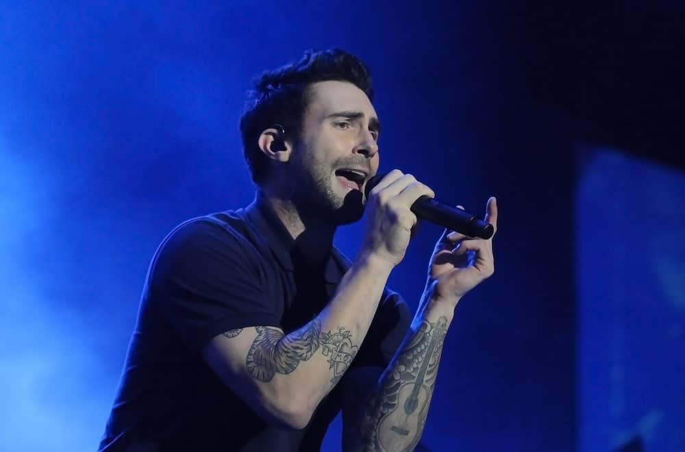 Singer Adam Levine from Maroon 5 rocked the stage of Rio de Janeiro on September 16, 2017 wearing a black collared shirt with his side-swept pompadour fade hairstyle and five o'clock shadow.
