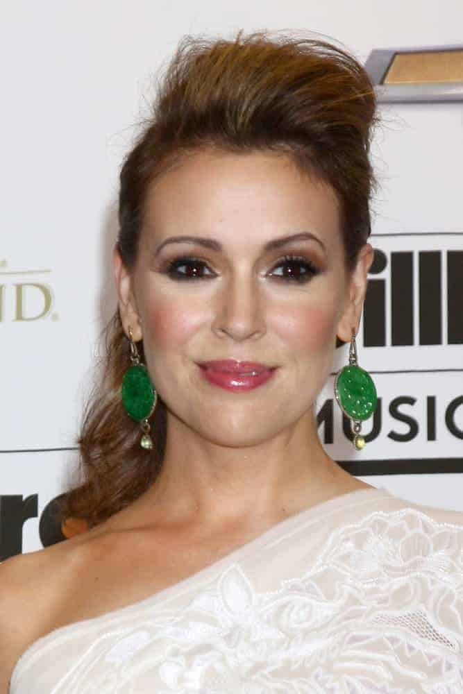 Alyssa Milano exhibited a pompadour low wavy ponytail that's elegantly funky and just perfect for the Billboard Music Awards 2013 on May 19, 2013. It was incorporated with green statement earrings and a white floral dress.