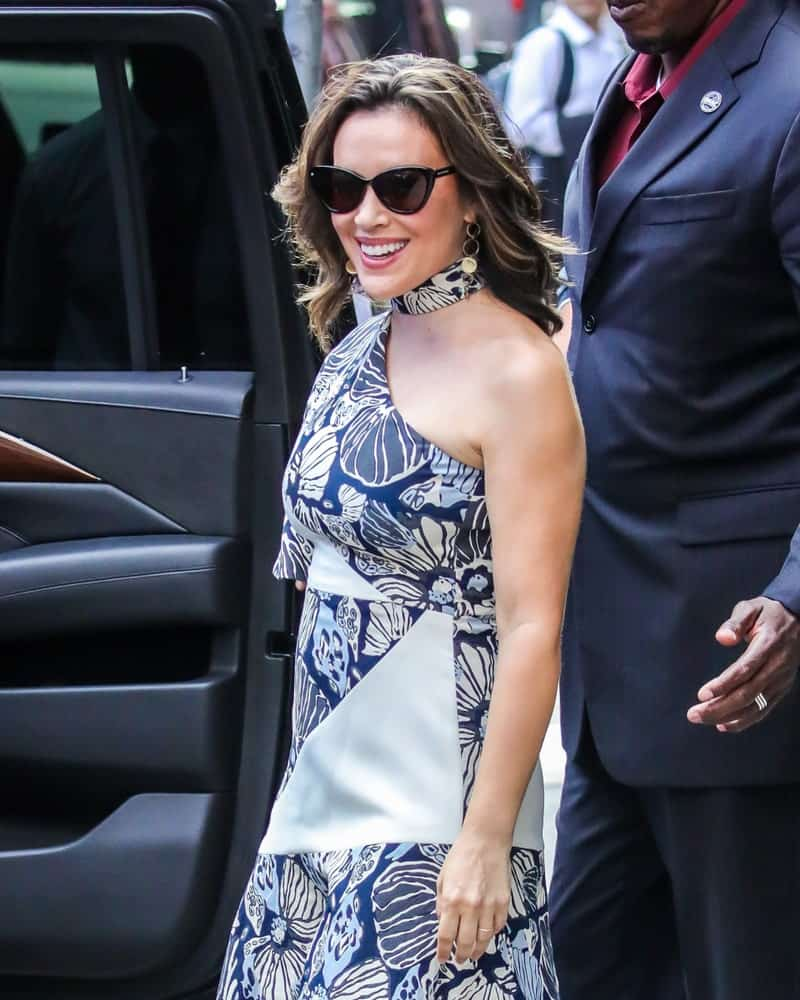 Alyssa Milano was spotted on August 6, 2018, in New York City wearing a floral print dress and black shades along with her tousled highlighted waves.