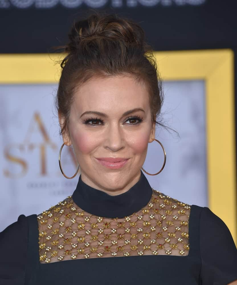 "Alyssa Milano had a messy upstyle hairstyle emphasizing her hoop earrings and turtleneck dress at the ""A Star Is Born"" Los Angeles Premiere on September 24, 2018."
