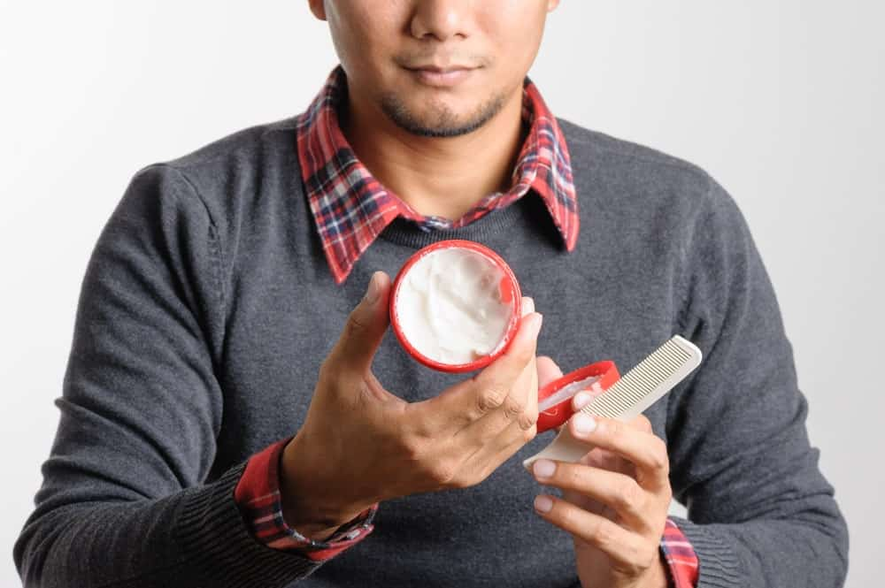 Man holding a tub of wax and a comb.