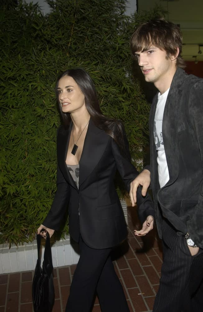 Demi Moore and Ashton Kutcher wore matching smart casual clothes at the opening of designer Stella McCartney's first Los Angeles store on September 28, 2003. Kutcher paired this with a tousled and wavy fringe hairstyle.