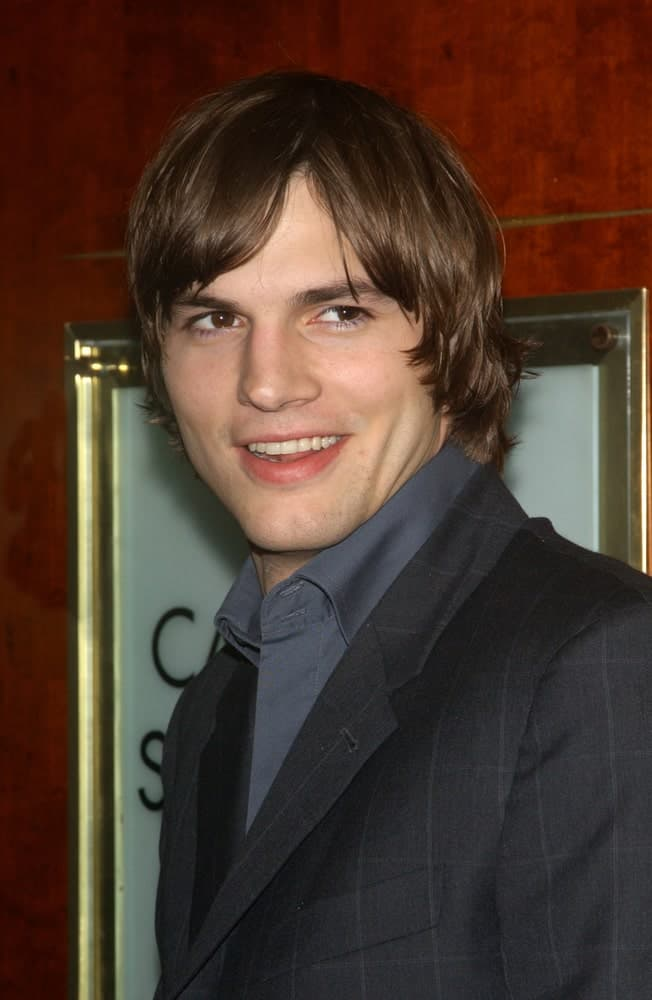Actor Ashton Kutcher's long and layered dark brown hair was side parted at the 65th Annual Will Rogers Pioneer of the Year Dinner honoring Walt Disney CEO Michael Eisner on December 4, 2003.