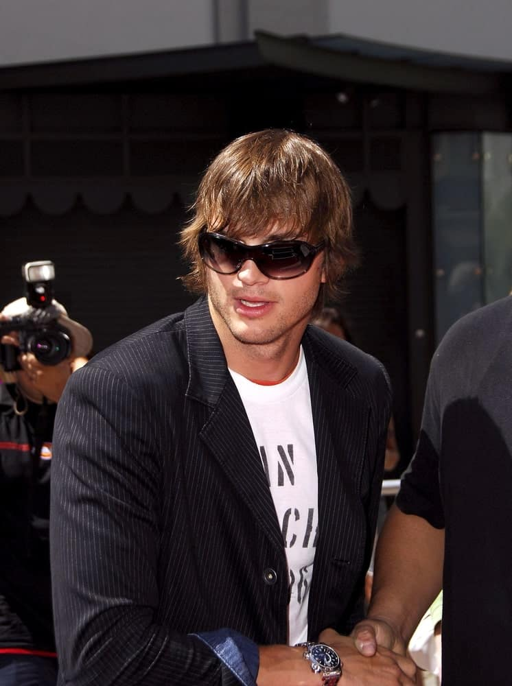 Ashton Kutcher was at the induction ceremony for Kevin Costner's hand and footprint ceremony in Hollywood, CA on September 06, 2006. His long and wavy hairstyle was dyed brown with a flippy finish at the side and bangs.