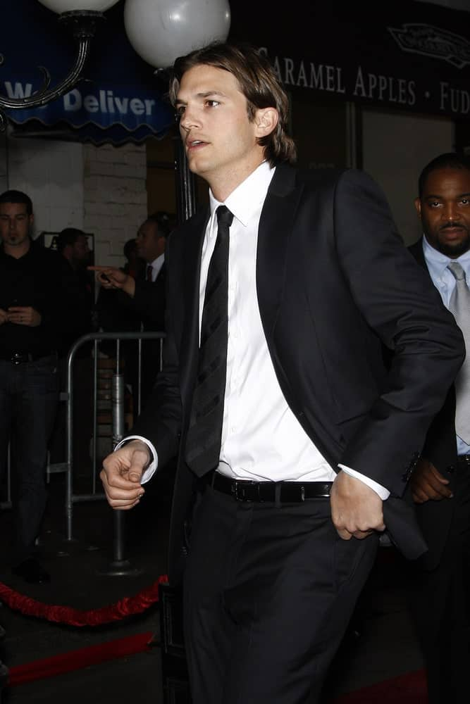 Ashton Kutcher balanced his classy black suit with a casual long highlighted hairstyle with a mullet at the premiere of 'No Strings Attached' at the Regency Village Theater in Los Angeles, CA on January 11, 2011.