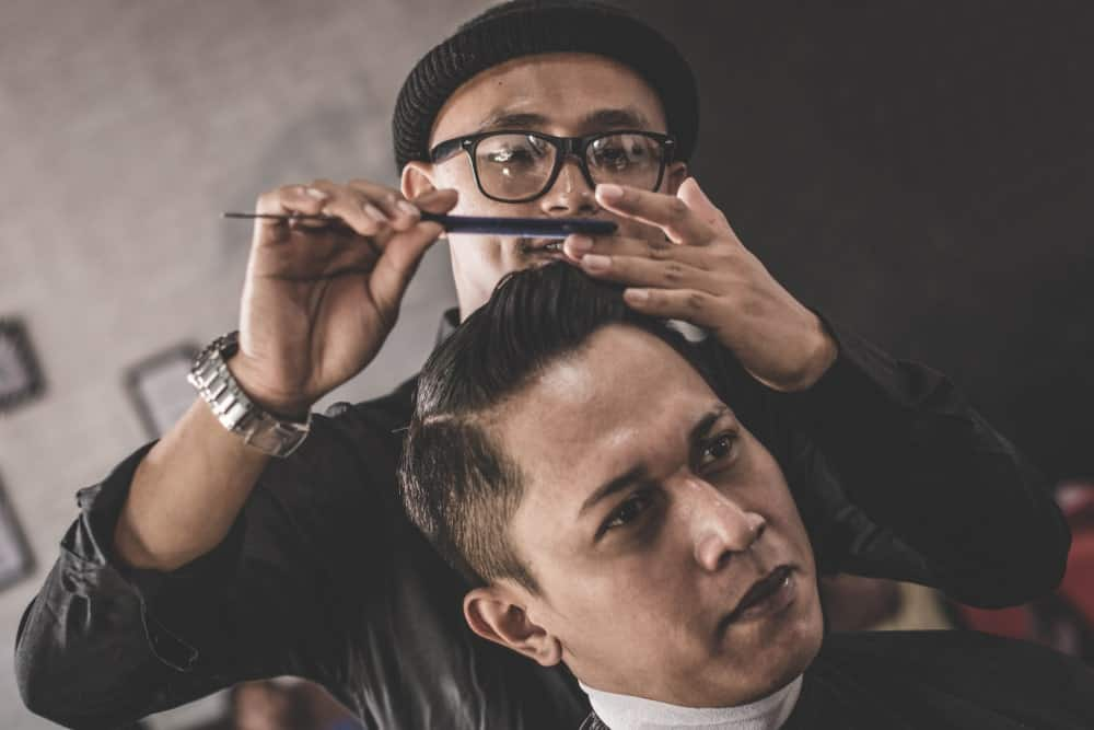 Barber styling man's hair with pomade and a comb.