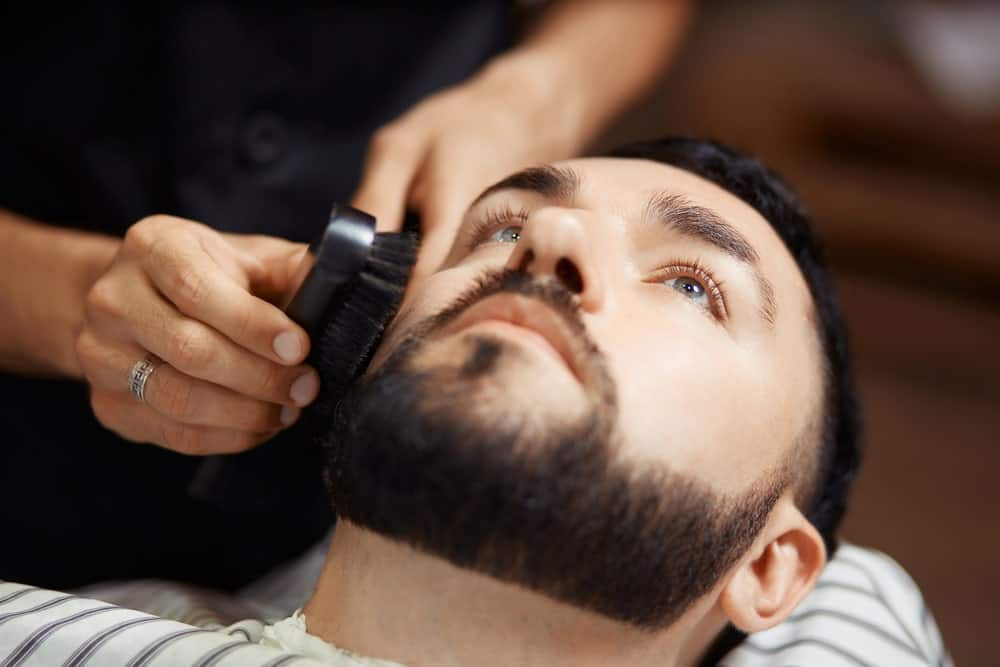 Man lying on a barber shop chair while the barber brushes his well-maintained beard.