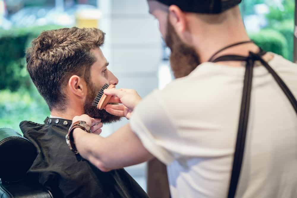 Man in a barber shop with a nice haircut and a well-maintained beard. His barber is brushing his facial hair.