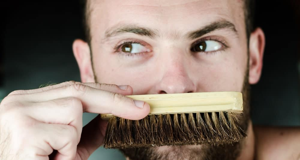 A close up shot of this man looking sideways and covering his mouth with a beard brush.