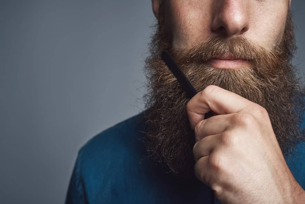 Man with thick beard in a blue shirt, combing his beard.