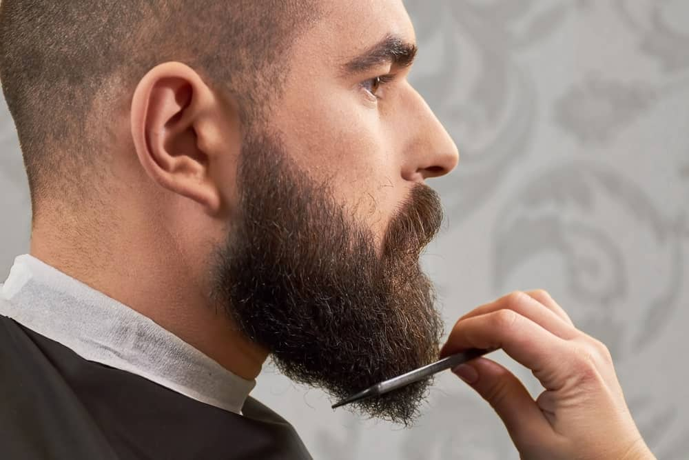 A side view of a man with thick beard in a barber shop, combing his beard.
