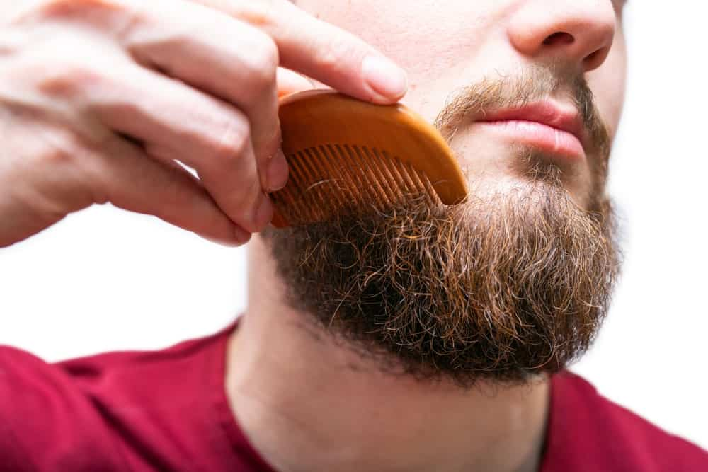 This man in a red shirt combs his beard gently.