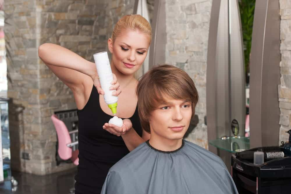 Blonde hairstylist applying mousse to a long haired man.