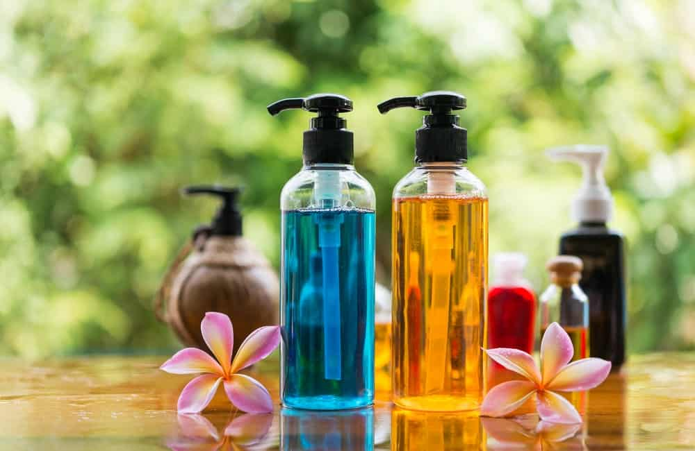 A focused look at these blue and orange colored body wash with two flower petals on both sides.