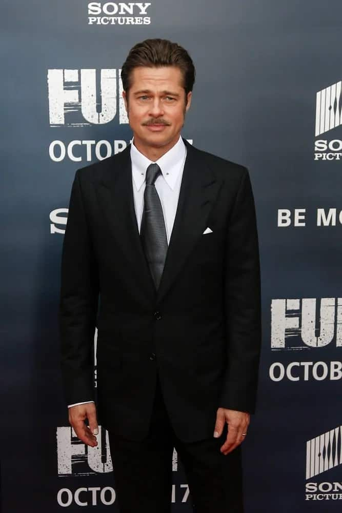 """Brad Pitt brushed his hair back for a pompadour style to pair with his mustache at the world premiere of """"Fury"""" at the Newseum last October 15, 2014, in Washington DC."""